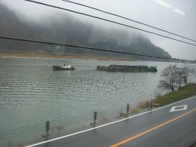 円山川を行く土砂運搬船と、それを曳くタグボート