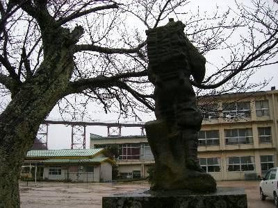 小学校校庭の二宮金次郎像と余部鉄橋